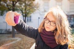 Schöne blonde Jugendliche, die Foto am Telefon macht Stockbilder