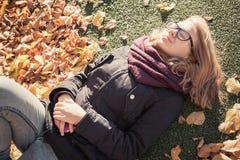 Schöne blonde Jugendliche, die in herbstlichen Park legt Lizenzfreie Stockfotografie