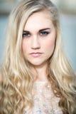 Schöne blonde Jugendliche mit blauen Augen Stockfotografie
