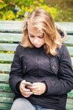 Schöne blonde Jugendliche mit Smartphone Lizenzfreie Stockfotos