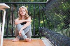 Schöne blonde Jugendliche sitzt auf Balkon Stockfoto