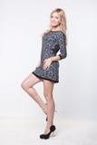 Schöne blonde junge Dame, die im Kleid aufwirft Stockbilder