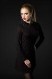 Schöne blonde junge Dame im schwarzen Kleid auf schwarzem Hintergrund Lizenzfreie Stockfotos