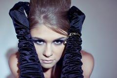 Schöne blonde junge Frau in den langen schwarzen Handschuhen Stockbild