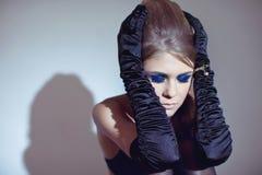 Schöne blonde junge Frau in den langen schwarzen Handschuhen Stockfoto