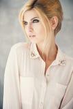 Schöne blonde junge Frau in der zufälligen Art Art- und Weisebaumuster im goldenen Kleid Stockbild