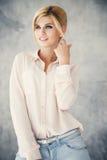 Schöne blonde junge Frau in der zufälligen Art Art- und Weisebaumuster im goldenen Kleid Lizenzfreie Stockbilder