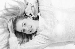 Schöne blonde junge Frau, die auf dem Bett glücklich liegt Stockfoto