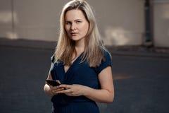 Schöne blonde junge Frau, die auf der Straße mit Telefon steht Aufflackern für Text und Design Lebensstilmädchen mit Smartphone i Stockbilder