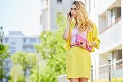 Schöne blonde junge Frau, die auf die Straße geht Stockbilder
