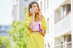 Schöne blonde junge Frau, die auf die Straße geht Stockfoto