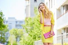 Schöne blonde junge Frau, die auf die Straße geht Stockfotos
