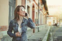 Schöne blonde junge Frau, die auf die Straße, sprechend am Telefon geht Lizenzfreie Stockbilder