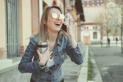 Schöne blonde junge Frau, die auf die Straße, sprechend am Telefon geht Lizenzfreies Stockfoto