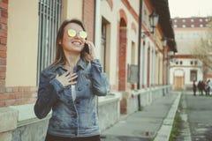 Schöne blonde junge Frau, die auf die Straße, sprechend am Telefon geht Stockfoto
