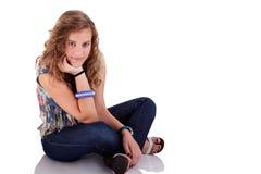 Schöne blonde junge Frau, die auf Fußboden sitzt Lizenzfreie Stockfotografie