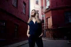 Schöne blonde junge Frau, die auf die Straße geht Aufflackern für Text und Design Lebensstilmädchen in der Stadt Stockfotografie