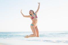 Schöne blonde junge Frau, die auf Strand springt Lizenzfreie Stockfotografie