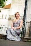 Schöne blonde junge Frau, die das Sitzen der modernen Kleidung trägt Lizenzfreie Stockfotos