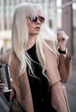 Schöne blonde junge Frau, die draußen mit Kaffee aufwirft Lizenzfreie Stockfotografie