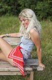 Schöne blonde junge Frau, die draußen sitzt Lizenzfreies Stockbild