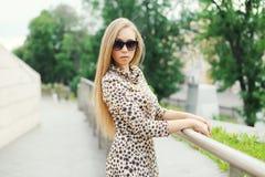 Schöne blonde junge Frau, die ein Leopardkleid und -Sonnenbrille trägt Stockbilder