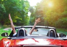 Schöne blonde junge Frau, die ein Sportauto fährt Stockfoto