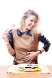Schöne blonde junge Frau, die an einem Tisch mit einer Platte von den Sushi u. von Essstäbchen halten Hand auf Bauch sitzt Lizenzfreie Stockbilder