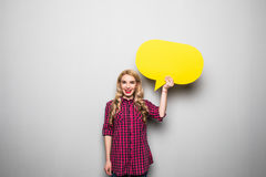 Schöne blonde junge Frau, die gelbe leere Spracheblase über grauem Hintergrund hält Stockfotografie