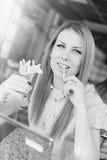 Schöne blonde junge Frau, die herein Pommes-Frites isst Lizenzfreies Stockfoto