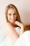 Schöne blonde junge Frau, die im Bett glücklich sich entspannt Lizenzfreies Stockfoto
