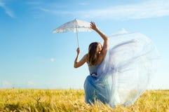 Schöne blonde junge Frau, die langes blaues Ballkleid trägt und den weißen Spitzeregenschirm sich lehnt oben auf Weizenfeld hält Stockfoto