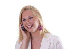 Schöne blonde junge Frau, die mit Telefon lächelt Lizenzfreie Stockfotos