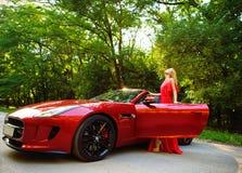 Schöne blonde junge Frau, die nahe einem Sportauto steht Stockbild