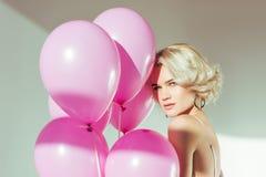 schöne blonde junge Frau, die rosa Ballone hält und Kamera betrachtet Lizenzfreie Stockfotografie