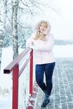 Schöne blonde junge Frau, die rosa Jacke und Blue Jeans im Winter trägt Lizenzfreie Stockfotos