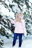 Schöne blonde junge Frau, die rosa Jacke und Blue Jeans nahe bei schneebedeckten Kieferniederlassungen trägt Lizenzfreie Stockbilder