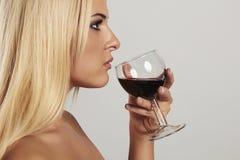 Schöne blonde junge Frau, die Rotwein trinkt Mädchen mit Make-up weinglas Stockfoto
