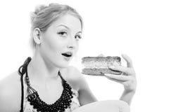 Schöne blonde junge Frau, die Schokoladenkuchen isst Lizenzfreie Stockfotos