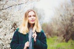 Schöne blonde junge Frau, die vor wunderbarer Blüte steht Stockfoto