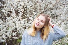 Schöne blonde junge Frau, die vor wunderbarer Blüte steht Lizenzfreie Stockbilder
