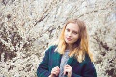 Schöne blonde junge Frau, die vor wunderbarer Blüte steht Stockbilder
