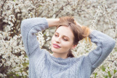 Schöne blonde junge Frau, die vor wunderbarer Blüte steht Lizenzfreies Stockbild