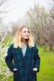 Schöne blonde junge Frau, die vor wunderbarer Blüte steht Stockfotos