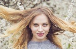 Schöne blonde junge Frau, die vor wunderbarer Blüte steht Stockfotografie