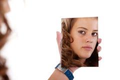 Schöne blonde junge Frau, die zu einem Spiegel schaut lizenzfreie stockfotos