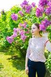 Schöne blonde junge Frau, die zwischen blühendem Fliederbusch steht Lizenzfreies Stockfoto