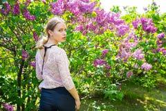Schöne blonde junge Frau, die zwischen blühendem Fliederbusch steht Lizenzfreie Stockfotos