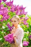 Schöne blonde junge Frau, die zwischen blühendem Fliederbusch steht Stockfotografie