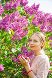 Schöne blonde junge Frau, die zwischen blühendem Fliederbusch steht Lizenzfreies Stockbild